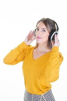 A mulher loura feliz sorri com os fones de ouvido na cabeça que olha a câmera vestida na camisa amarela isolada no branco