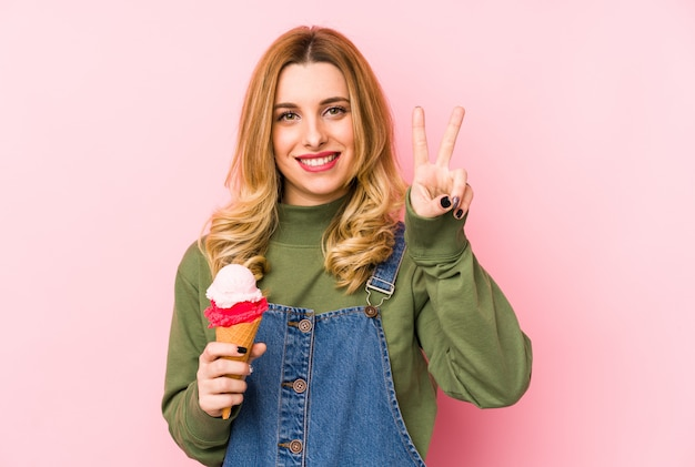 A mulher loura nova que come um gelado isolou mostrar o número dois com dedos.