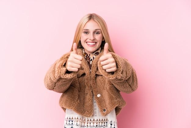 A mulher loura nova que veste um casaco contra um fundo cor-de-rosa com polegares levanta, elogios sobre algo, apoia e respeita o conceito.