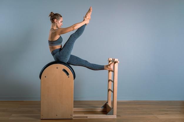 A mulher loura positiva bonita que executa pilates exercita, treinando no equipamento do tambor.