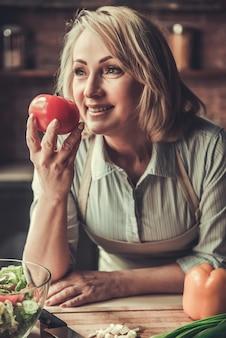 A mulher madura bonita no avental está cheirando o tomate.