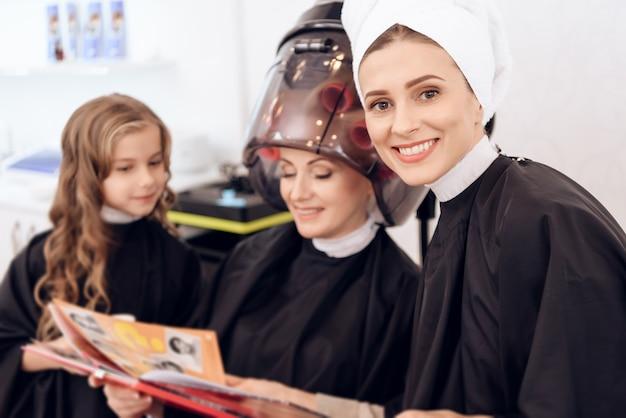 A mulher madura com encrespadores de cabelo seca o cabelo.