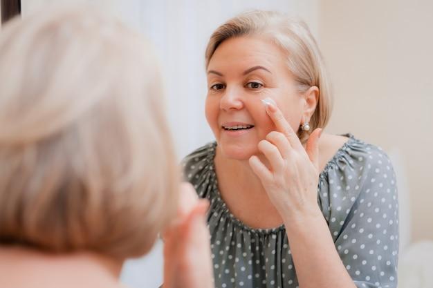 A mulher madura saudável feliz no espelho aplica o creme cosmético hidratando antienvelhecimento no rosto, senhora de meia-idade e cuidados com a pele limpa macia