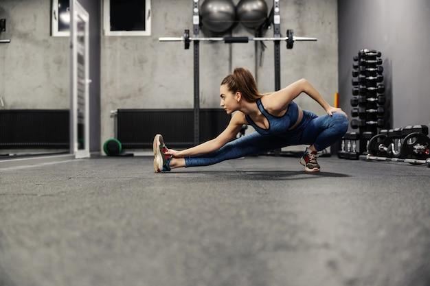 A mulher magra e em forma alonga os músculos de todo o corpo dando passos e inclinando o corpo e com uma mão em direção ao pé