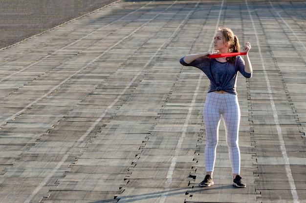 A mulher magro nova no sportswear que faz agachamentos exercita com elástico em uma trilha revestida preta do estádio