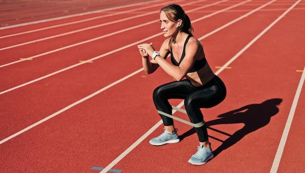 A mulher magro nova no sportswear que faz agachamentos exercita com elástico em uma trilha revestida vermelha do estádio