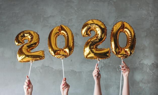 A mulher mãos segurando balões de números 2020 no fundo da parede de concreto cinza