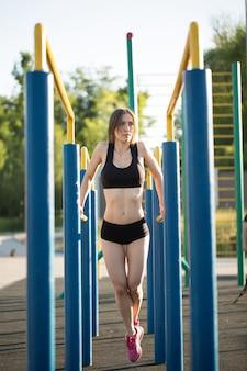 A mulher morena para praticar esportes em aparelhos de ginástica