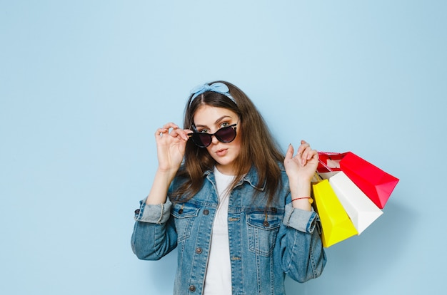 A mulher moreno bonita com óculos de sol aprecia as compras que fez em um fundo azul