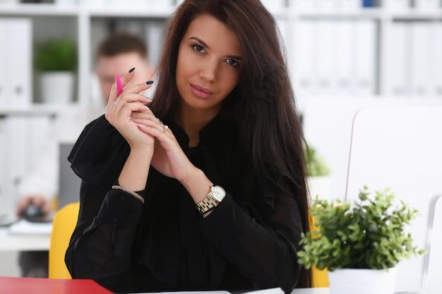 A mulher moreno de sorriso bonita senta-se na mesa de trabalho