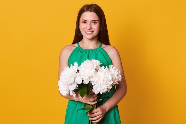 A mulher moreno europeia que veste o vestido de verão verde que guarda o ramalhete das peônias brancas floresce em ambas as mãos, levantando isolado no amarelo, estando no alto astral. sping conceito.