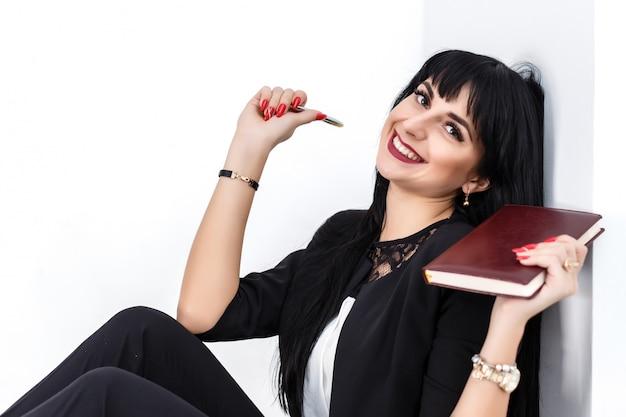 A mulher moreno feliz bonita nova que guarda um caderno vestiu-se no terno de negócio preto que senta-se em um assoalho no escritório, sorrindo, olhando a câmera.