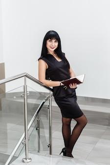 A mulher moreno feliz bonita nova vestiu-se em um terno de negócio preto que trabalha com um caderno, estando em um escritório, sorrindo.