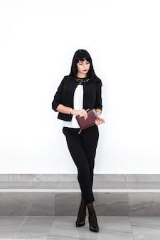 A mulher moreno séria bonita nova com um livro de nota vestiu-se em um terno de negócio preto que está contra a parede branca no escritório.
