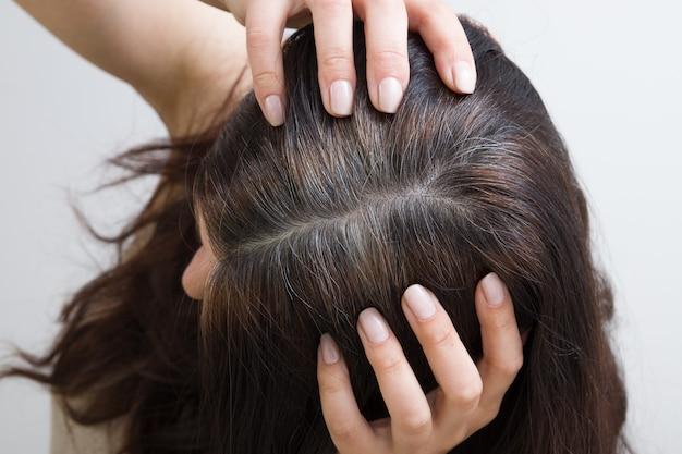 A mulher mostra cabelos grisalhos na cabeça. cabelo com fragmentos de cabelo grisalho, raízes do cabelo que requerem tingimento