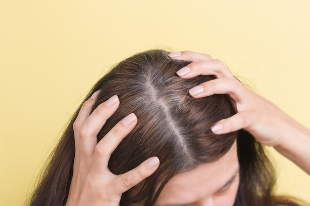 A mulher mostra cabelos grisalhos na cabeça. cabelo com fragmentos de cabelo grisalho requerendo coloração em um fundo amarelo