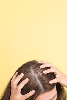 A mulher mostra cabelos grisalhos na cabeça com fragmentos de cabelos grisalhos que precisam de coloração em um amarelo ...