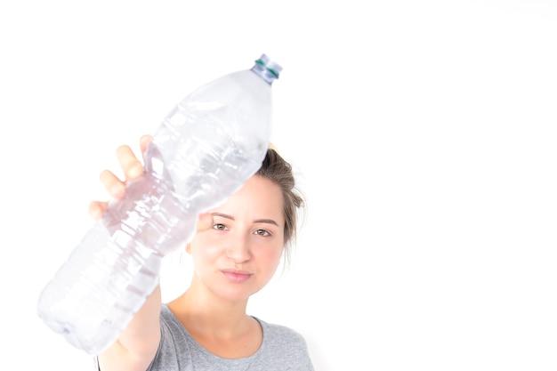 A mulher mostra e mantendo a garrafa plástica reciclável isolada no fundo branco.