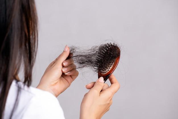 A mulher mostra sua escova com cabelo danificado da perda longa.