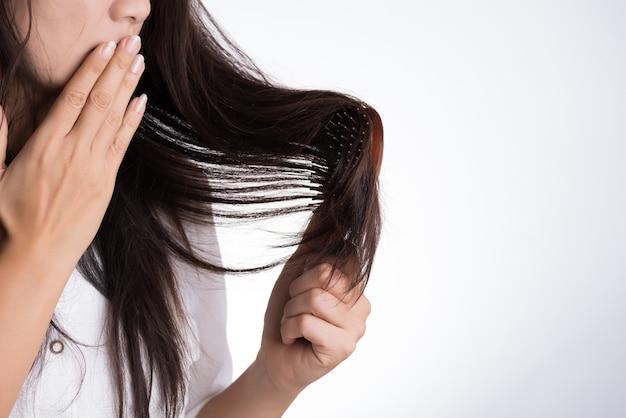 A mulher mostra sua escova com cabelo danificado da perda longa
