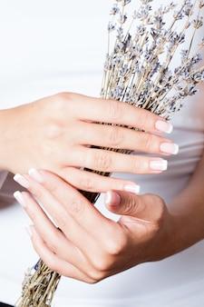A mulher mostra uma bela manicure francesa segurando alfazema seca