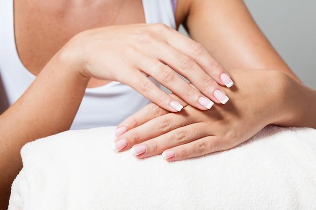 A mulher mostra uma linda manicure francesa colocando as mãos uma na outra