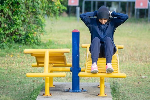 A mulher muçulmana que veste a roupa e o hijab escuros cobre seus exercícios do cabelo no parque.