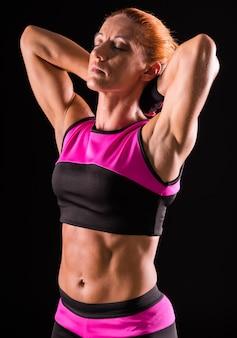 A mulher muscular do bodybuilder está estando com olhos fechados.