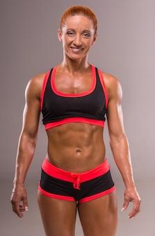 A mulher muscular do bodybuilder está olhando a câmera.