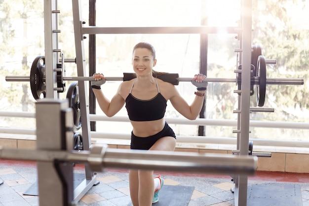 A mulher muscular que levanta peso no gym ao fazer lunges. apta atleta feminina malhando no health club, vestindo sutiã preto e curto, parece feliz, posando com sorriso.