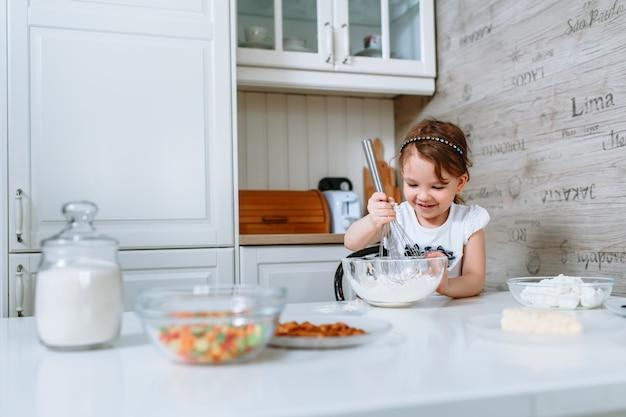 A mulher na cozinha bate a massa com um batedor de bolo