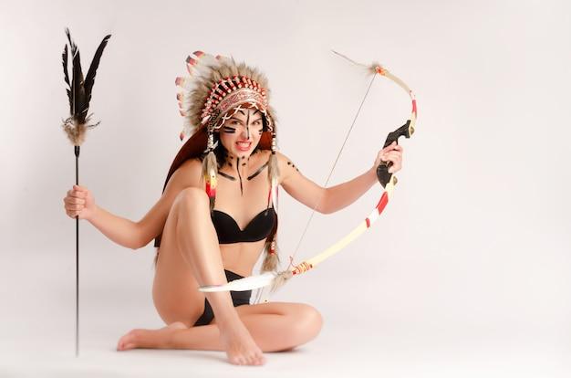 A mulher na imagem dos povos indígenas da américa com arco e flecha posa sentada sobre um fundo claro