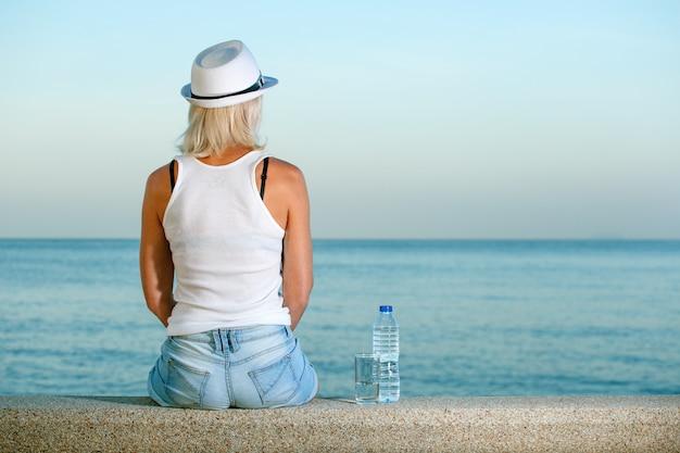 A mulher na praia com uma garrafa de água que olha no mar no país tropical. viagem, conceito de férias.