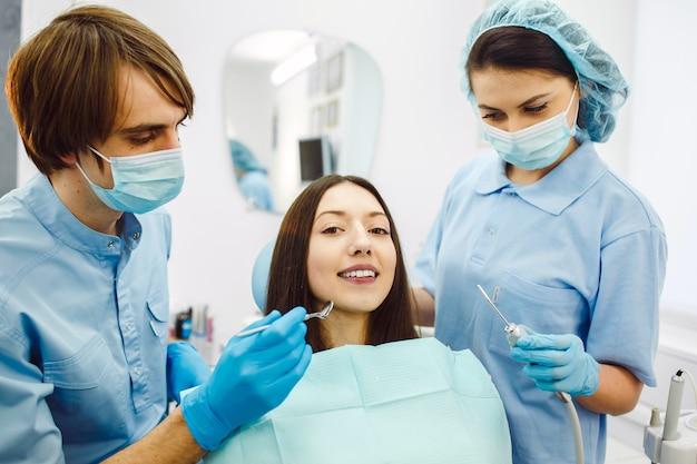 A mulher na recepção no dentista com assistente