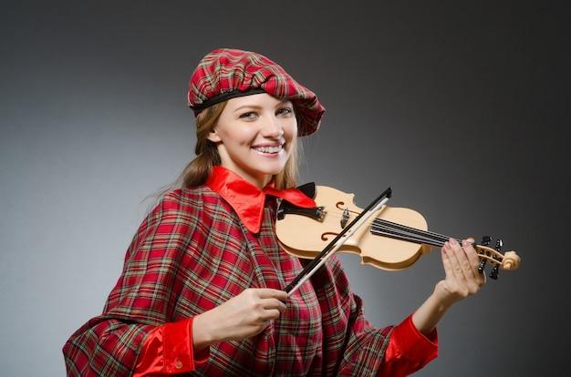 A mulher na roupa escocesa no conceito musical