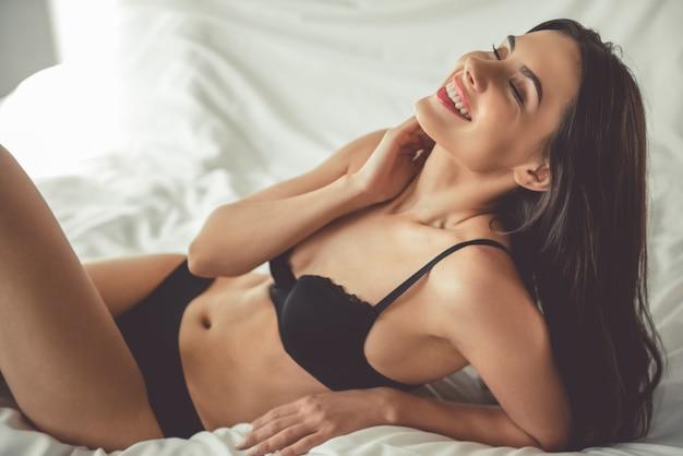 A mulher na roupa interior preta está sorrindo ao encontrar-se na cama.