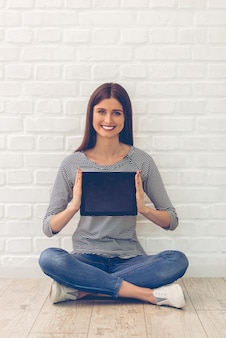 A mulher na roupa ocasional está mostrando uma tabuleta digital.