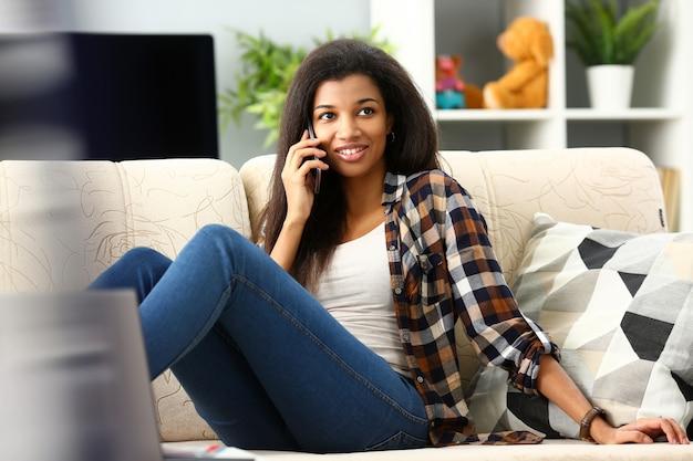 A mulher negra de sorriso segura o telefone móvel da mão em casa