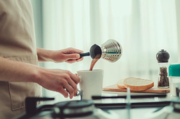 A mulher no avental prepara o café turco saboroso quente do cezve no café da manhã na cozinha em casa.