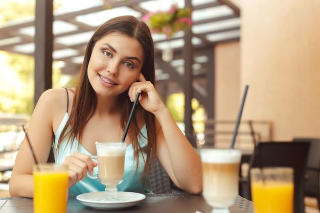 A mulher no café se senta em uma mesa