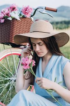 A mulher no chapéu que guarda a peônia cor-de-rosa perto da bicicleta com uma cesta das flores e aprecia a natureza.