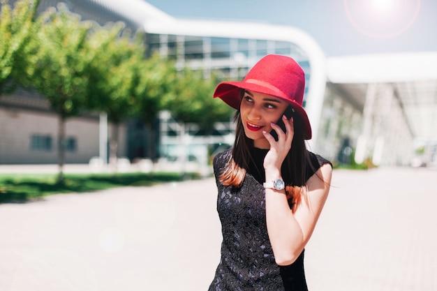 A mulher no chapéu vermelho segura o telefone no braço a pé