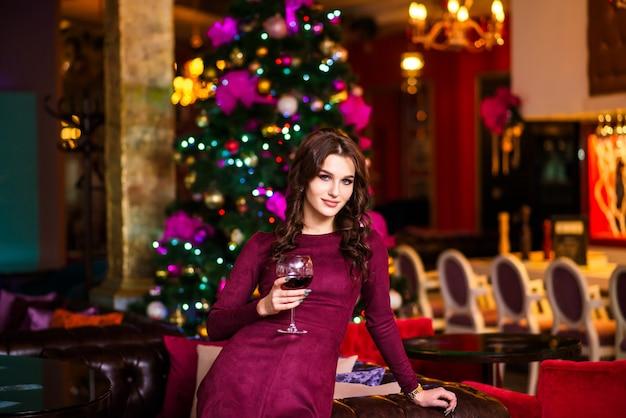A mulher no restaurante com um vidro do champanhe por o ano novo.