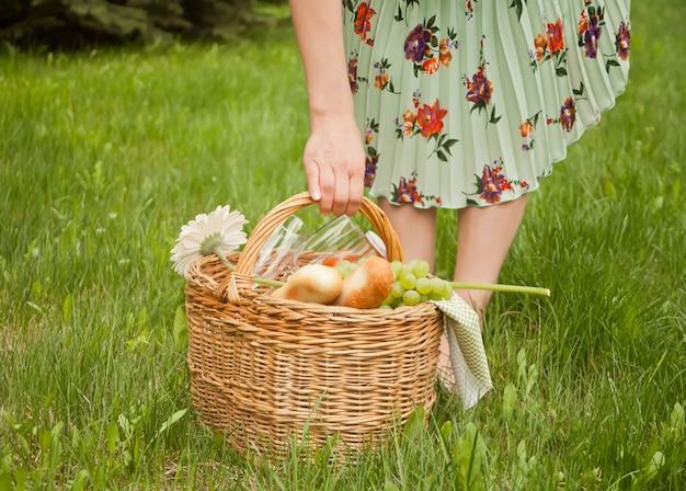 A mulher no suporte de piquenique na grama verde e prende a cesta do piquenique em uma mão.