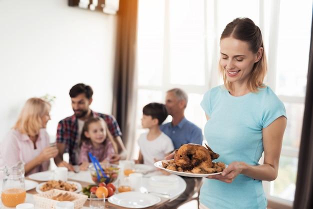 A mulher no t-shirt azul está estando no fundo com chiken.
