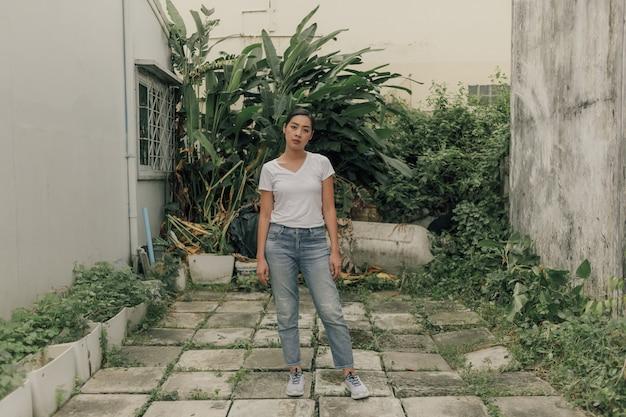 A mulher no t-shirt e no brim brancos está no jardim do quintal.