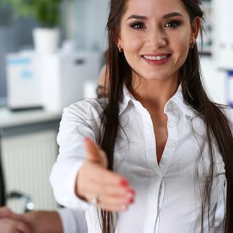 A mulher no terno dá a mão como olá no escritório