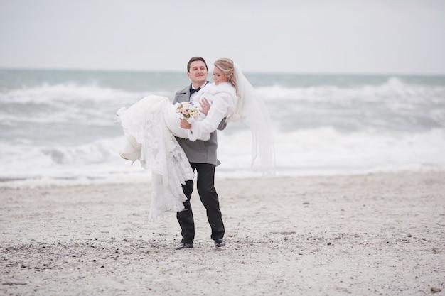 A mulher nos braços do marido na praia