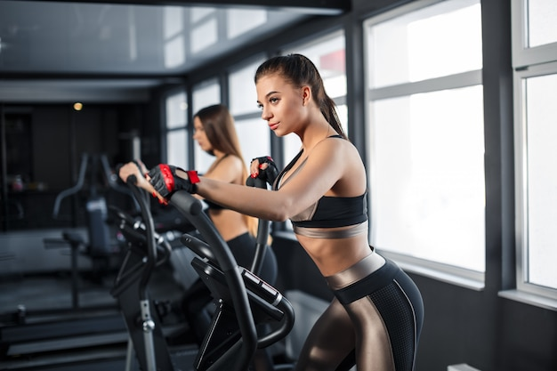 A mulher nova atrativa dos esportes está dando certo no gym. fazendo treinamento cardio na esteira. correr em esteira