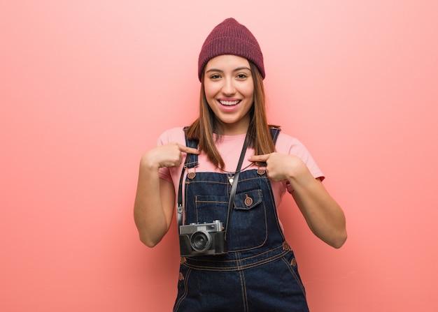A mulher nova bonito do fotógrafo surpreendida, sente bem sucedida e próspera